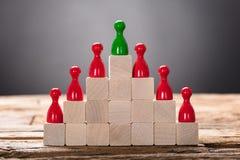 Figurine verdi e rosse del pegno sistemate sui blocchi di legno fotografia stock