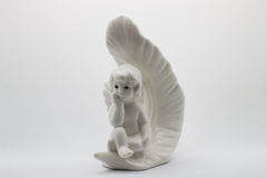 Figurine white angel with feather. Statuette of an angel on white background Royalty Free Stock Image
