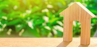 Figurine of a wooden house with a large doorway on a green background . Concept of real estate, purchase and sale of housing. Affo stock photography