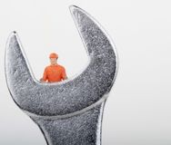 Figurine of a worker on a big monkey wrench Royalty Free Stock Images