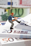 Figurine of worker climbing on stack of euro note Royalty Free Stock Photography