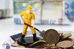 Figurine worker with shovel standing on pile of euro coins Royalty Free Stock Photography