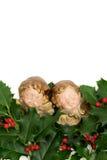 2 figurines ангела на зеленых листьях падуба и красных ягодах Стоковые Фото