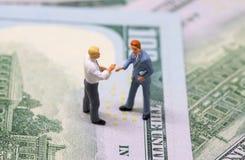 Figurines бизнесменов тряся руки на наличных деньгах Крошечные модели бизнесменов на предпосылке денег стоковые изображения rf