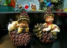 Figurines мальчика и девушки при шляпа конуса сосны играя на конусах сосны Брайна Стоковые Изображения RF