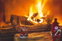 2 figurines Санта Клауса стоя на журналах камином Стоковые Фото
