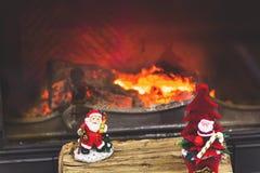 2 figurines Санта Клауса стоя на журналах камином Стоковая Фотография RF