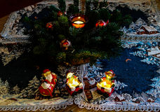 Figurines северного оленя Санта Клауса между свечами, игрушками и ветвями рождественской елки Стоковое Фото