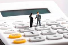 2 figurines стоя на калькуляторе стоковая фотография