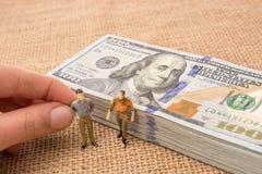 Figurines людей около пачки банкноты доллара США Стоковая Фотография RF