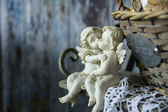 Figurines angels sitting on a bench near the wicker basket. Romance on the background of old boards Stock Photo