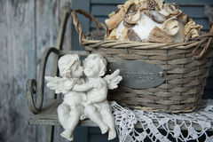 Figurines angels sitting on a bench near the wicker basket. Romance on the background of old boards Stock Images