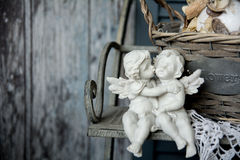 Figurines angels sitting on a bench. Romance on the background of old boards Royalty Free Stock Photos