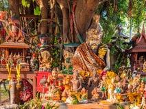 Figurines autour d'un arbre sacré en Thaïlande Images libres de droits
