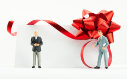 Figurines of businessmen with gift card Royalty Free Stock Photo