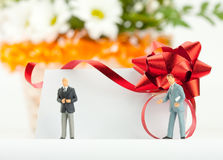 Figurines of businessmen with gift card Stock Photos