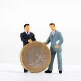 Figurines of businessmen with one euro coin Stock Images
