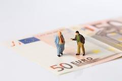 Figurines d'hommes d'affaires se tenant sur d'euro billets de banque Image stock