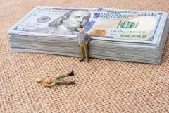 Figurines d'hommes près du paquet du billet de banque de dollar US Image stock