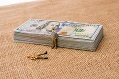 Figurines d'hommes près du paquet du billet de banque de dollar US Image libre de droits
