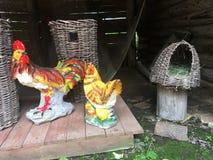 Figurines de porcelaine des coqs se tenant sur la rue près des paniers en osier Image libre de droits