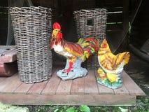 Figurines de porcelaine des coqs se tenant sur la rue près des paniers en osier Photo libre de droits