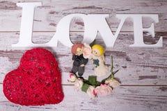 Figurines des jeunes mariés qui symbolisent l'engagement pour aimer Images libres de droits
