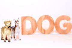 Figurines of dogs and the inscription dog in wooden letters royalty free stock image
