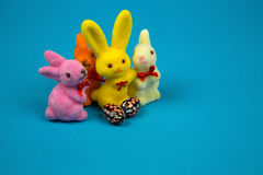 Figurines Easter bunnies and Easter eggs. Four colorful figurines Easter bunnies and two Easter eggs on blue cardboard background.Close, horizontal view Stock Photos