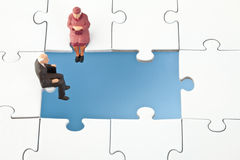 Figurines of elderly people sitting on jigsaw piece. Copy space Royalty Free Stock Images