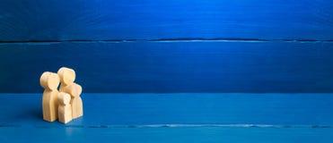 Figurines en bois d'une jeune famille sur un fond blanc Concept d'un jeune m?nage mari? fort et sain Un couple affectueux image stock