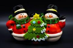 Figurines faites main de bonhommes de neige d'isolement sur le fond noir Décoration de Noël photographie stock