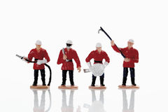 Figurines of fire brigade standing in row holding hosepipe Royalty Free Stock Image