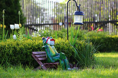 Figurines of frogs. On the little bench under the lantern Stock Photography