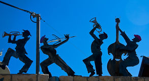 Figurines of a happy band against the skies Stock Images