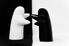 Figurines noires et blanches de porcelaine sur un fond blanc/noir Photographie stock