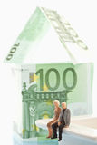 Figurines sitting in front of house of 100 Euro notes. On white background Royalty Free Stock Photo