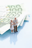 Figurines standing by 100 euro notes. With reflections Royalty Free Stock Image