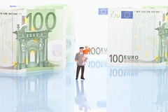Figurines standing in front of 100 euro note. With reflections Stock Photos