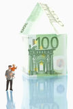 Figurines standing in front of house of 100 euro notes. On white background with reflections Stock Photography