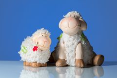 Figurines of two funny sheep in front of a blue background royalty free stock photo