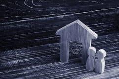 Figurka drewniany dom z dwa ludźmi popiera kogoś popiera kogoś na tle czarne deski - obok - Pojęcie nieruchomość, zakup i sprzeda Obraz Stock