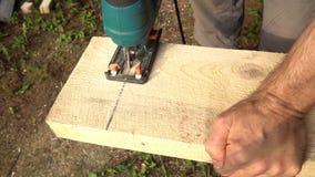 Figuurzaag die een houten raad 4K zagen stock video
