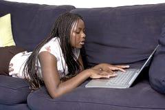 Fijación adolescente en el sofá con la computadora portátil Fotos de archivo libres de regalías