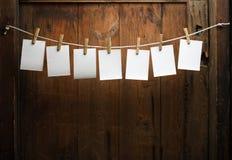 Fijación del papel de la foto a rope con los contactos de ropa fotografía de archivo