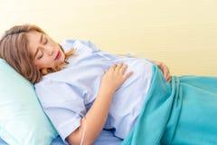 Fijación embarazada joven en la cama en la preparación del hospital imagenes de archivo