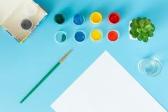 Fijado para pintar pinta la hoja de papel blanca con las pinturas suculentas, multicoloras verdes y el cepillo en un fondo azul c fotos de archivo libres de regalías