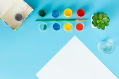 Fijado para pintar pinta la hoja de papel blanca con las pinturas suculentas, multicoloras verdes y el cepillo en un fondo azul c foto de archivo libre de regalías