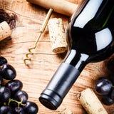 Fijando con la botella de vino rojo, de uva y de corchos Fotografía de archivo