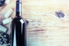 Fijando con la botella de vino rojo, de uva y de corchos Carta de vinos concentrada Imágenes de archivo libres de regalías